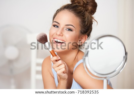 Gorgeous young brunette woman applying makeup.