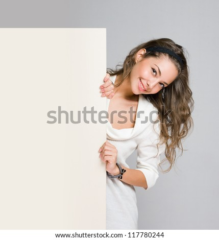 Gorgeous young brunette woman holding blank white billboard.