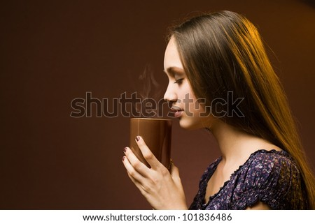 Gorgeous young brunette woman with cup of hot beverage.