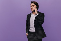 Gorgeous young businessman with brunette hair, light shirt and trendy striped suit, talking on phone and looking away. Man posing against violet pastel background