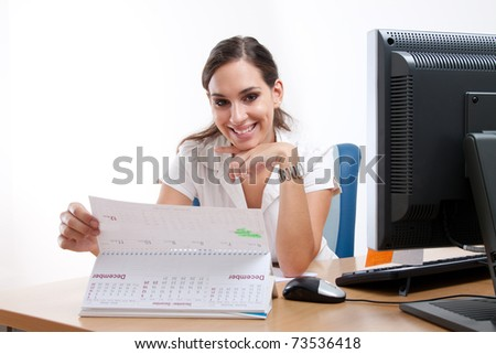 Gorgeous young businesswoman behind her desk. Checking her schedule.