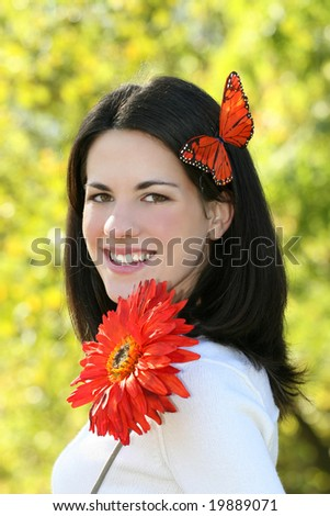 Gorgeous young Caucasian woman outdoors, in a park, with a bright red flower and a red butterfly