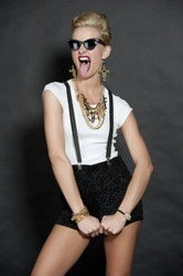 Gorgeous young female blonde wearing a white top, trendy black shorts with suspenders, gold necklace, and hip sunglasses on a back background in a studio sticking her tongue out.