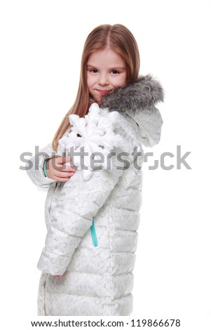 Gorgeous young girl holding huge white snowflake in winter overcoat