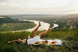 Gorgeous young girl in a white sundress lying on grass and having a picnic in a picturesque place. Romantic picnic. Happy beautiful girl on the nature picnic. Relaxing girl in nature.