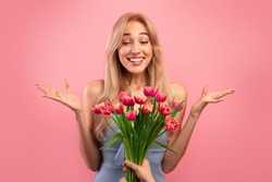 Gorgeous young lady feeling excited to receive bunch of tulips for Woman's Day on pink studio background. Lovely blonde getting bouquet of flowers for spring holiday. Festive concept
