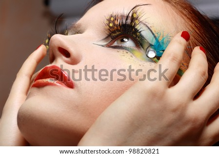 Gorgeous Young model beautiful women with perfect art make up and long false eyelashes made from feathers