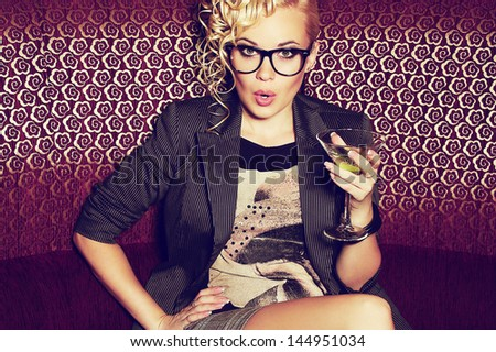 Gorgeous young superstar with cocktail in her hand disturbed by paparazzi in the night club (lounge bar). Hipster style. Copy-space. Indoor shot