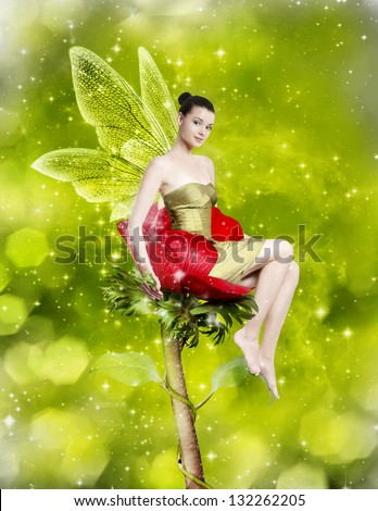Gorgeous young woman as spring fairy sitting on red flower on green background