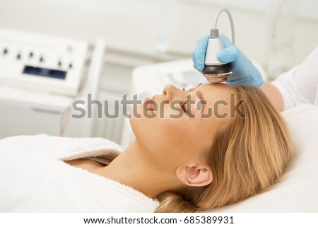 Gorgeous young woman lying with her eyes closed relaxing while receiving facial ultrasonic treatment at modern beauty spa clinic salon therapist therapy pampering skin refreshing procedure cosmetology #685389931
