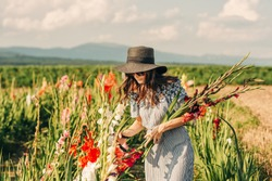 Gorgeous young woman picking flowers in a field, wearing summer dress, black straw hat and sunglasses