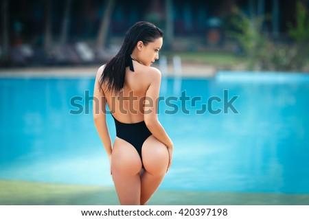Gorgeous young woman posing in bikini near pool