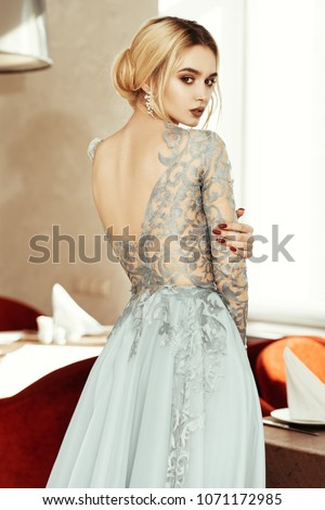 5ad94bbd0 Gorgeous young woman posing in restaurant dressed in evening or wedding  chic gown. Beauty,
