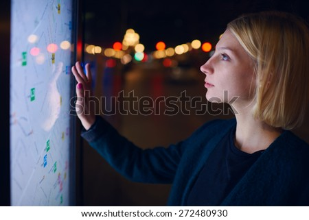 Gorgeous young woman standing front big digital screen with basic city street map data, female touching sensitive display of modern smart city bus stop for check her location into the night