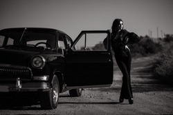 Gorgeous young woman wearing flared trousers and elegant transparent blouse standing on the road at the open door of her vintage car. Black and white shot