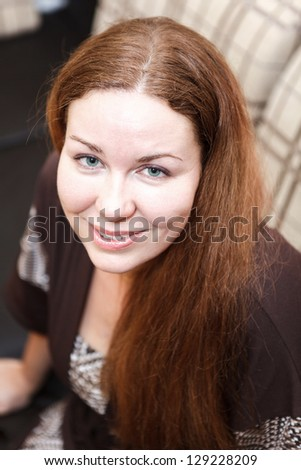 Gorgeous young woman with beautiful hair looking at camera