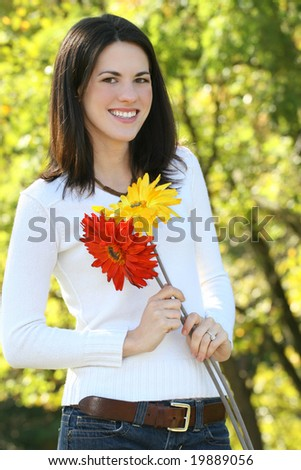 Gorgeous young woman with bright flowers outdoors in a park, forest