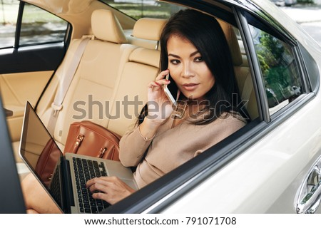 Gorgeous young woman with laptop sitting in car and talking on the phone #791071708