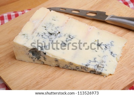 Gorgonzola, Italian blue cheese on cheeseboard with knife.