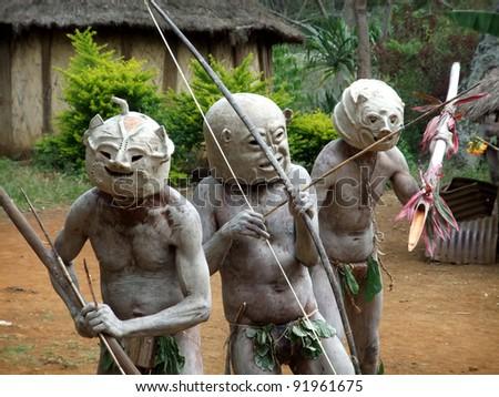 GOROKA, PAPUA, NEW GUINEA - SEPTEMBER 16: Mudmen warriors clasp their weapons at Goroka Tribal Festival  in Goroka, Papua New Guinea on September 16, 2011