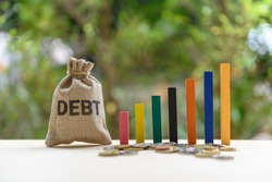Gorvernment or public  national debt concept : Color wood bar graph, coin and a debt bag on a table, depicts the government collects taxes less than spending, the difference is called deficit or debt