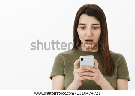 Gosh you never gues what posted online. Portrait of impressed and speechless girl using smartphone looking amazed and stunned at mobile phone screen with opened mouth from amazement over gray wall