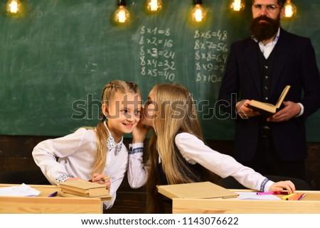 gossip whispering, little girls whispering gossip at school lesson. gossip whispering of two girls friends. gossip whispering concept. gossiping