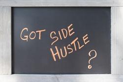 Got Side Hustle Sign handwritten on black board with wood frame for concept of Entrepreneurship