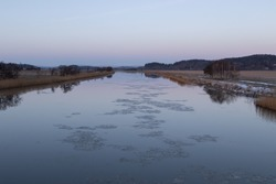 Gota river in western sweden with sheets of ice flowing in the water and hoar frost on the ground