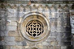 Gothic ancient round window, grey stone. Rosette window. Marigold window. Rose window.