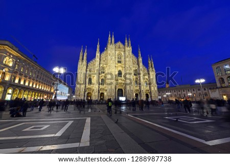 Gothic architecture of Milan Cathedral at night in Milan Italy with purposely blurred unrecognizable crowd of people in square