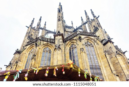 Gothic architectured St. Vitus Cathedral from bottom in a cloudy day. Easter ornamented wood stalls roof. Negative copy space, place for text. Prague, Czech Republic #1115048051