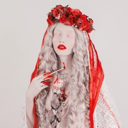 Gothic blonde woman vampire in flower wreath with pale skin and red lips. Brush in blood. Scary creepy succubus with long hair. Gothic succubus in wreath with ribbons. Scary blonde girl. Blood fingers
