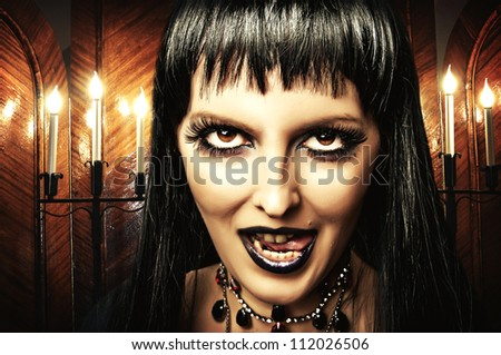 Gothic brunette woman witch with dark make-up and evil eyes