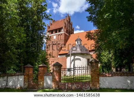 Gothic church of St. Anthony Abbot (Antoniego Opata) in Wozlawki, Warmia, Poland. The inscription on the cross means 'God bless you'.  Zdjęcia stock ©