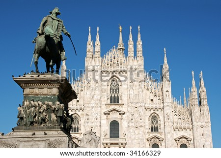Gothic facade of Milan Cathedral in Piazza del Duomo. It is the fourth largest church in the world. On the left the monument to king Vittorio Emanuele II.