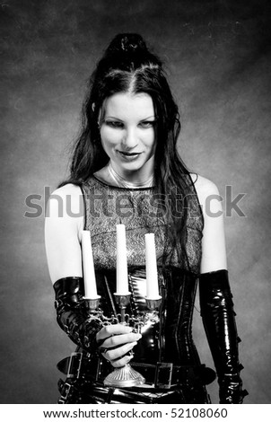 gothic girl in latex clothes with candlestick in hands