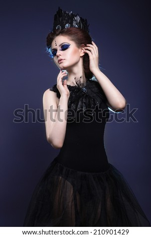 Gothic girl with a crown and a necklace of feathers and creative makeup. Picture taken in the studio