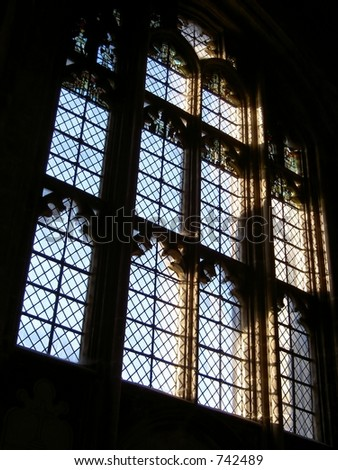 Gothic glass window in Winchester cathedral with early morning sun