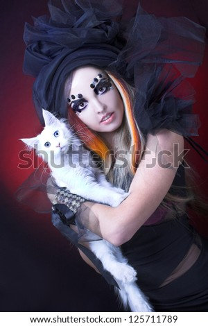 Gothic lady with artistic makeup posing witt white cat