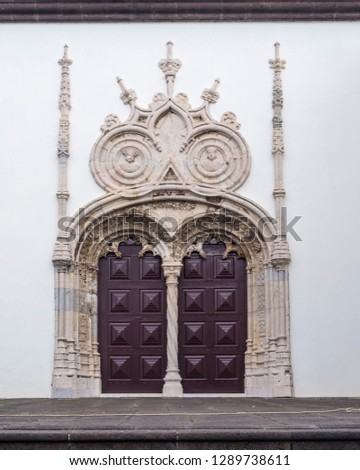Gothic portal door with Pinnacle decoration on white facade of churche in Ponta Delgada, Sao Miguel island, Azores