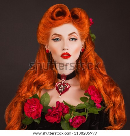 Gothic queen with red lips with stylish hairstyle in studio. Beauty redhead model with hairdo on black background. Renaissance perfect queen on a dark background. Gothic vampire with long red hair