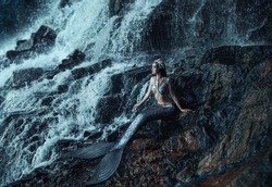 gothic real mermaid  resting on ocean shore. Wet Silver tail, the body is covered with scales. Creative costume clothes. Queen of sea, crown shells. Summer view landscape a huge waterfall rock stone