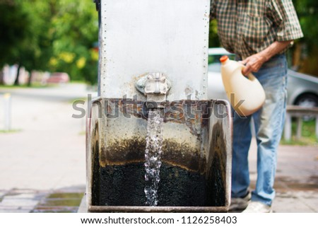Gothic spigot installed on a flowing artesian wellhead. Selective focus. The blurry contours of a partially visible man holding a plastic demijohn, in the nearest surroundings. #1126258403