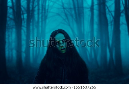 Gothic witch. Ghost in the fog. Girl in the paranormal world. Stranger forest in a fog. Mystical atmosphere. Dark wood. Mysterious road. Background wallpaper. Gloomy times. Dark background