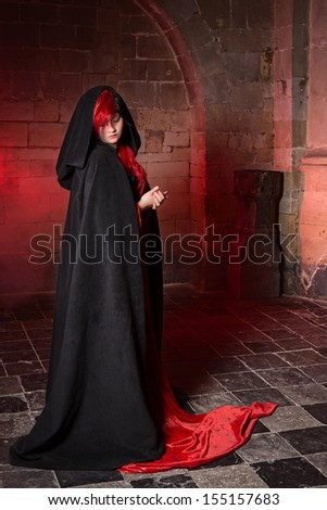 Gothic witch woman standing in a medieval castle