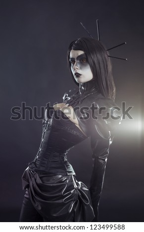 Gothic woman in black Victorian outfit wearing tight corset and bolero