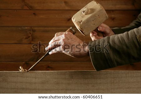 gouge wood chisel carpenter tool hammer in hand working wooden background