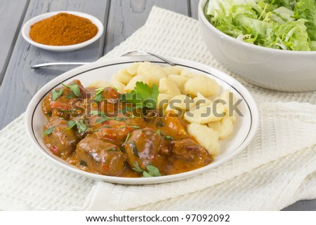 Goulash - Hungarian sausage stew served with homemade nokedli and green leaf salad - stock photo