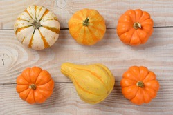Gourds and pumpkins from a high angle on a white rustic wooden table. Horizontal format.